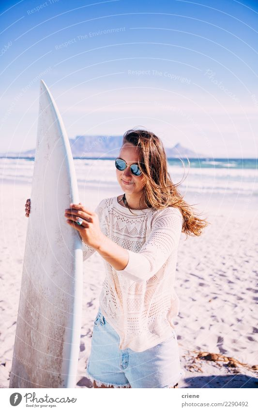 Young female adult carrying surfboard on beach Lifestyle Happy Leisure and hobbies Summer Beach Ocean Woman Adults Smiling Surfboard Surfing outdoor recreation