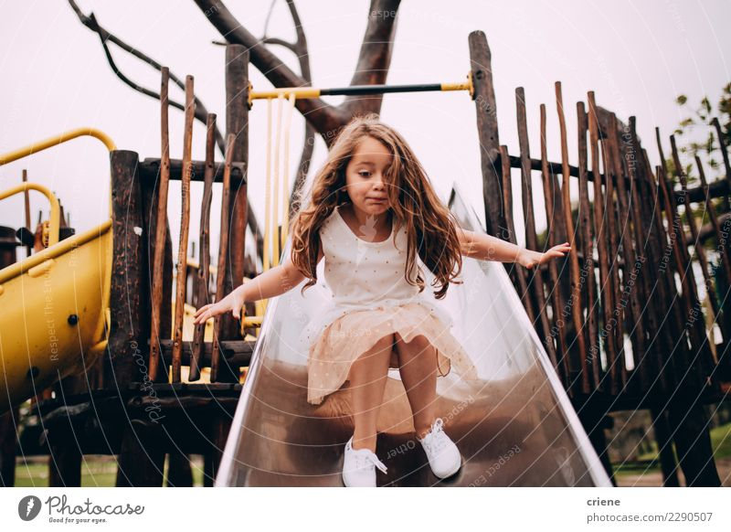 Little caucasian girl having fun on slide on playground Child Joy Lifestyle Emotions Small Happy Playing Infancy Cute Delightful Playground Caucasian