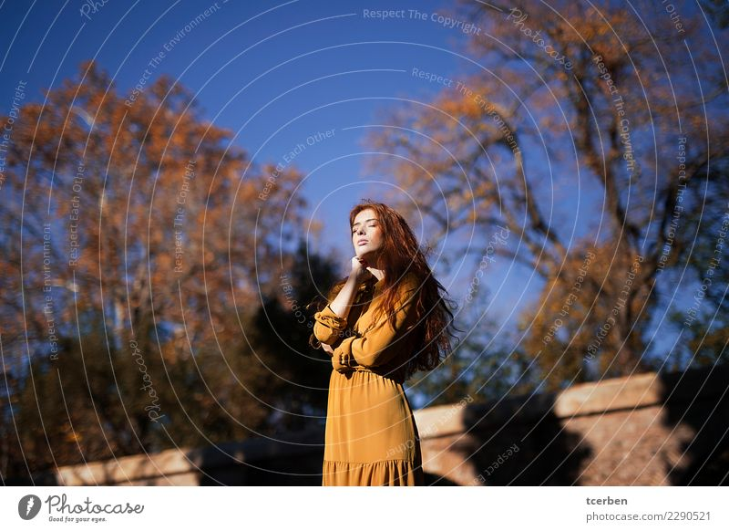 Autumnal portrait of redhead woman in the sun touching her neck Human being Sky Youth (Young adults) Old Young woman Blue Beautiful Sun Tree Loneliness Calm