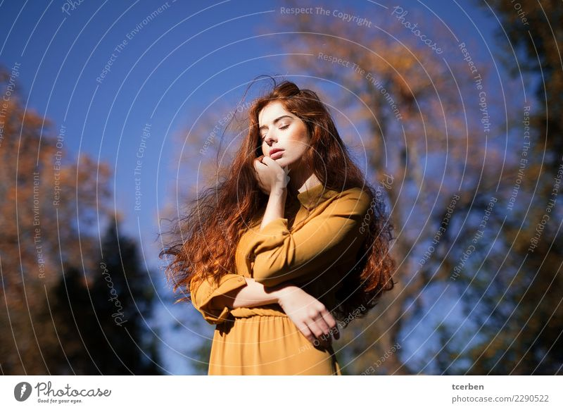 Autumnal portrait of redhead woman in the sun touching her face Human being Sky Nature Youth (Young adults) Young woman Blue Beautiful Sun Tree Calm
