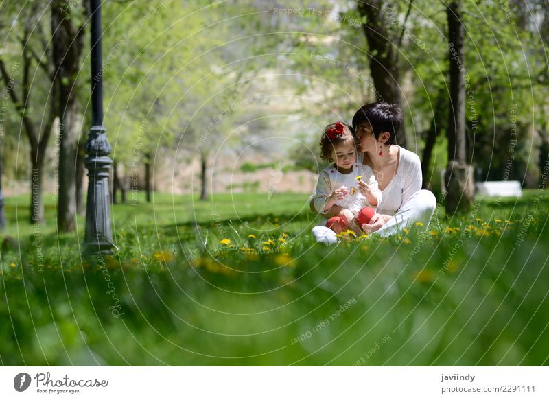 mother kissing her little daughter in urban park Child Woman Human being Flower Joy Adults Lifestyle Love Emotions Feminine Grass Family & Relations Small