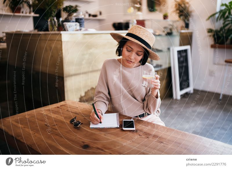 Asian young woman writing notes in notebook Drinking Table Music Work and employment Woman Adults Youth (Young adults) Musical notes Hat Paper Pen Listening Sit