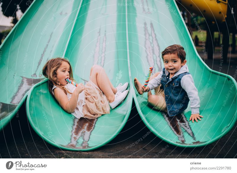 Cute caucasian siblings sitting on slide on playground Joy Eating Family & Relations Boy (child) Happy Infancy Smiling Delightful Playground Sister Caucasian