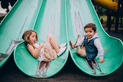 Cute caucasian siblings sitting on slide on playground Eating Joy Happy Boy (child) Sister Family & Relations Infancy Playground Smiling brother sweets