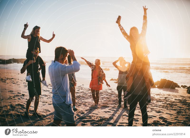 Group Of Happy Friends Dancing On Beach Party