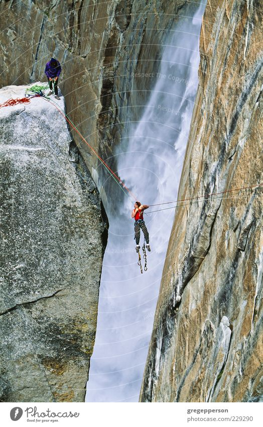 Rock climbing team reaching the summit. Human being Adults Mountain Sports Friendship Contentment Power Tall Adventure Rope Peak Climbing Trust Athletic Brave Balance