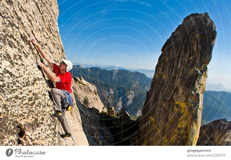Male rock climber clinging to a steep cliff. 1 Human being 30 - 45 years Adults Athletic Bravery Self-confident Power Willpower Adventure Resolve Fitness