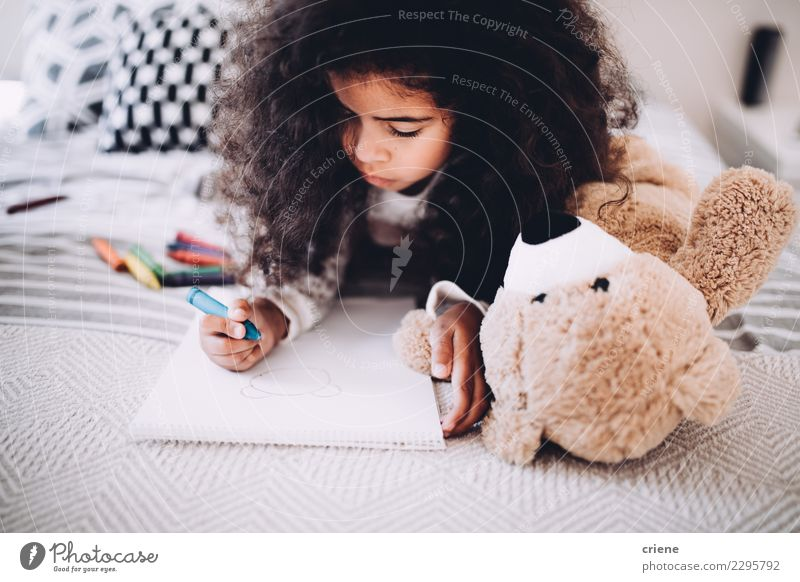 Little girl doing homework on bed at home Joy Happy Beautiful Child School Woman Adults Infancy Paper Smiling Dream Happiness Small Cute Black african drawing