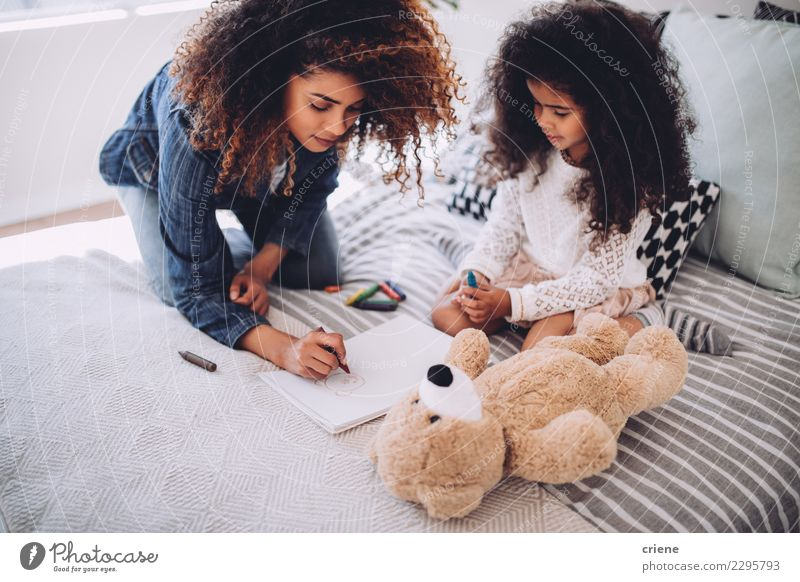 African mother helping daughter doing homework Happy Child Human being Woman Adults Parents Mother Family & Relations Infancy Art Paper Small Cute Black Colour