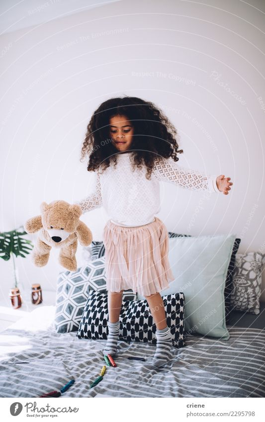 Little african girl jumping on bed with teddy bear Child Human being Beautiful White Joy Black Laughter Small Happy Playing Jump Infancy Happiness Cute Toys