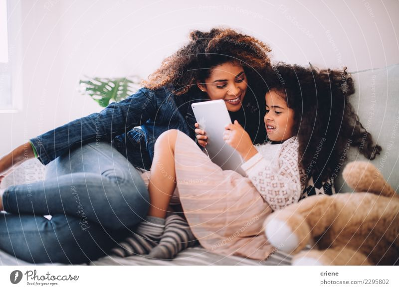 Happy mom and daughter using digital tablet together Child Woman Beautiful Black Adults Family & Relations Together Leisure and hobbies Infancy Technology Sit