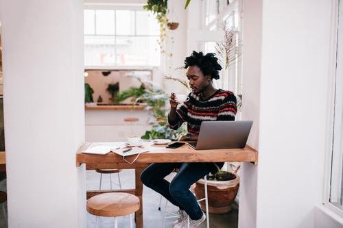 African young man working with laptop in coffee shop Coffee Shopping Happy Restaurant Work and employment Business Computer Notebook Technology Internet