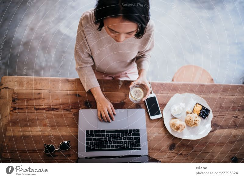 Young adult woman working on laptop in cafe Eating Breakfast Coffee Plate Lifestyle Table Work and employment Office Business PDA Computer Notebook Human being