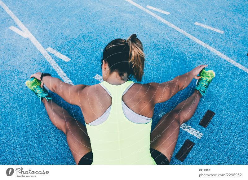 Fit Woman stretching on blue running track before run Lifestyle Sports Track and Field Success Jogging Stadium Racecourse Human being Adults Competition legs