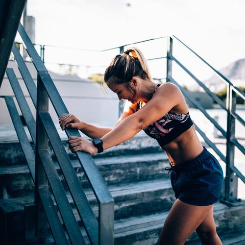 Fit smiling female adult resting after exhausting training Lifestyle Sports Woman Adults Fitness Bright Modern Determination Fatigue Resting running Practice