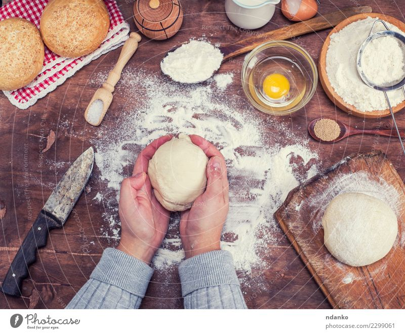 hands hold a ball of yeast dough Dough Baked goods Bread Bowl Knives Body Table Kitchen Arm Hand Sieve Wood Fresh Natural Above Brown White Yeast background
