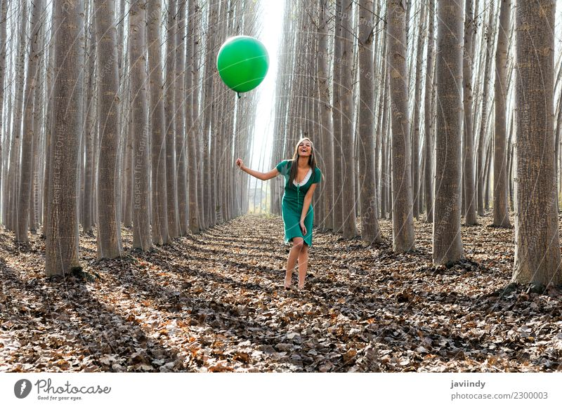 Girl laughing in the forest with green balloon and dress Joy Human being Young woman Youth (Young adults) Woman Adults 1 18 - 30 years Nature Autumn Tree Leaf
