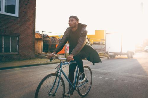 Young modern hipster riding bike trough urban city while sunset Modern Town City life Lifestyle Freedom Sunset Dusk Sneakers Transport Hipster Clothing Jacket
