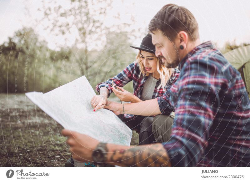 Young camping couple in nature searching way on map