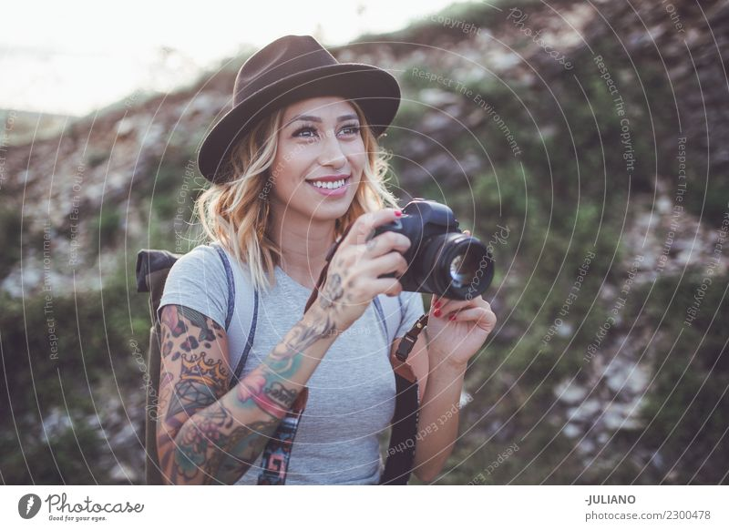 Young hiking woman is taking picture with camera of view