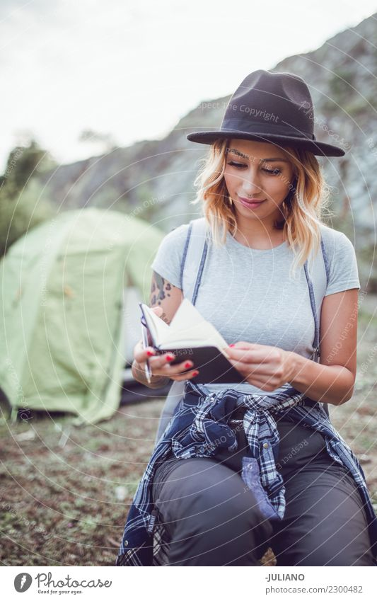 young hiking woman taking notes at camp Lifestyle Leisure and hobbies Vacation & Travel Trip Adventure Far-off places Freedom Camping Mountain Hiking