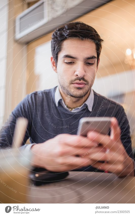 Young man at cafe looking at his phone Breakfast To have a coffee Communicate Lifestyle Shopping Leisure and hobbies PDA Human being Masculine