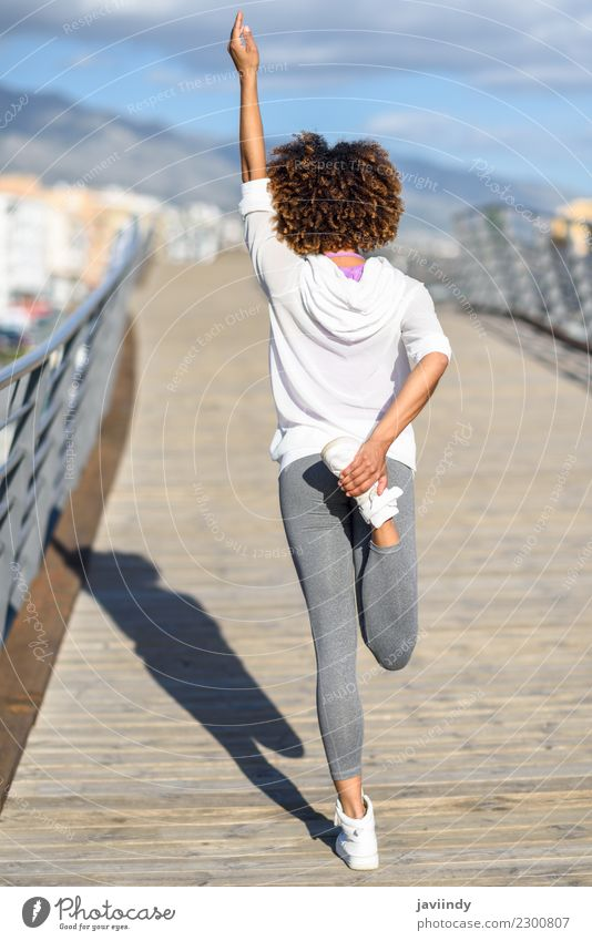 Young black woman doing stretching after running outdoors Lifestyle Beautiful Hair and hairstyles Wellness Leisure and hobbies Sports Jogging Human being