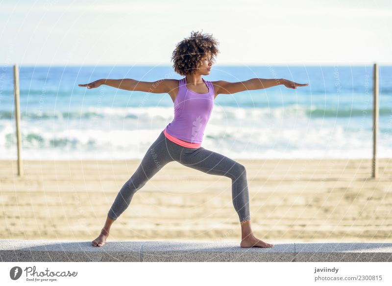 Black woman doing yoga in warrior pose in the beach. Lifestyle Beautiful Body Hair and hairstyles Wellness Relaxation Meditation Leisure and hobbies Beach Ocean
