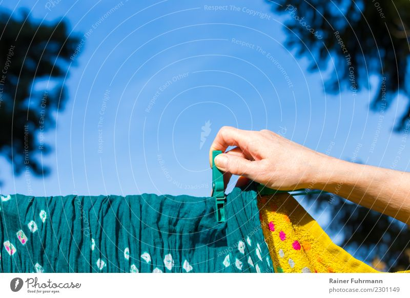 "a woman hangs laundry to dry on a clothesline Flat (apartment) Garden Human being Feminine Hand Cleanliness Purity ""wash Laundry housework role distribution"