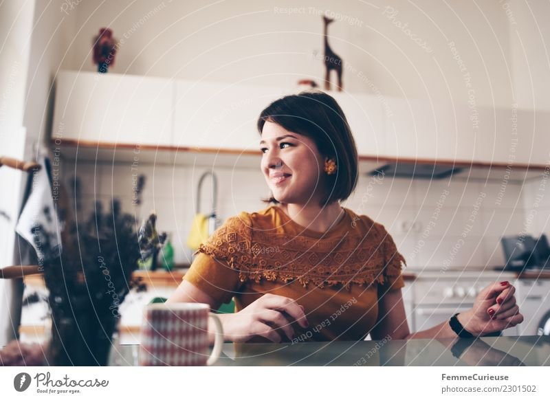Young woman sitting at a kitchen table Feminine Youth (Young adults) Woman Adults 1 Human being 18 - 30 years Living or residing Kitchen Kitchen Table Good mood
