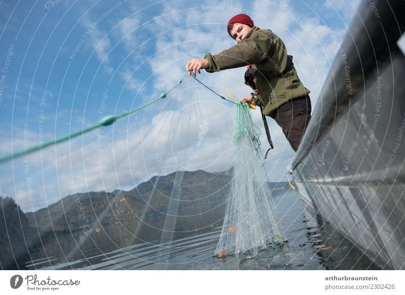 Young fisherman in a fishing boat at the lake catches up with his fishing net Food Fish Nutrition Slow food Healthy Eating Leisure and hobbies Fishing (Angle)