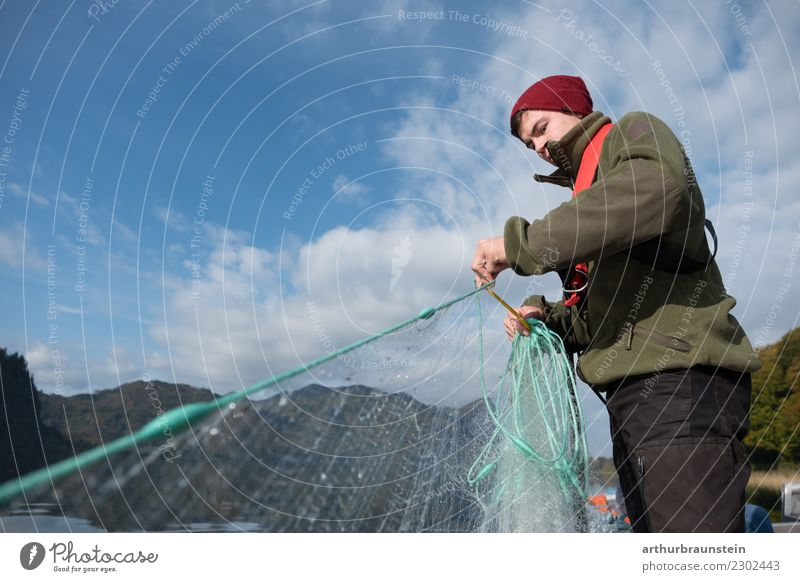 Young fisherman pulls in his fishing net youthful Fisherman Man Lake Water Blue sky Fishing net hobby Beautiful weather sunny teaching profession Apprentice