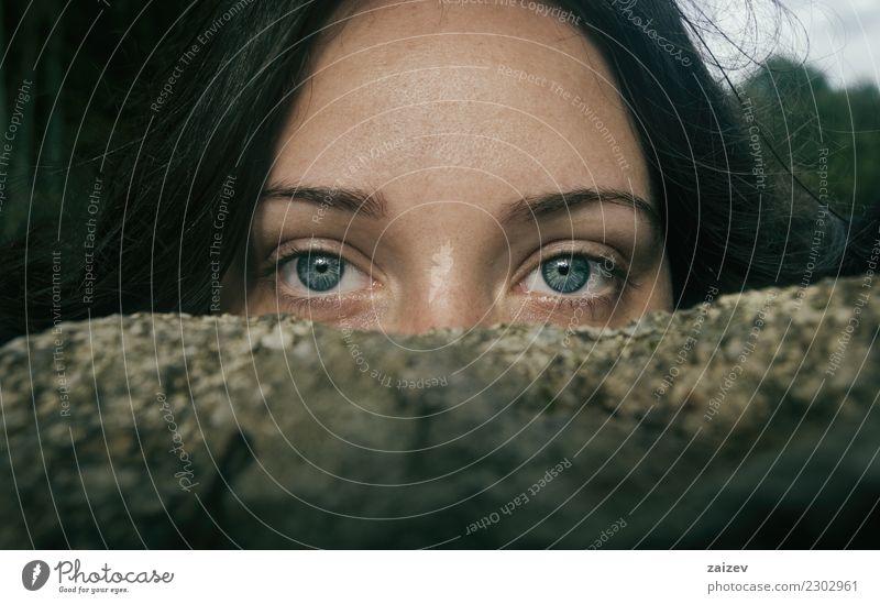 Chica de ojos azules y grandes mirando a camara por encima de una piedra tapandose la mitad de la cara Camera Woman Adults Stone Think Discover Exceptional