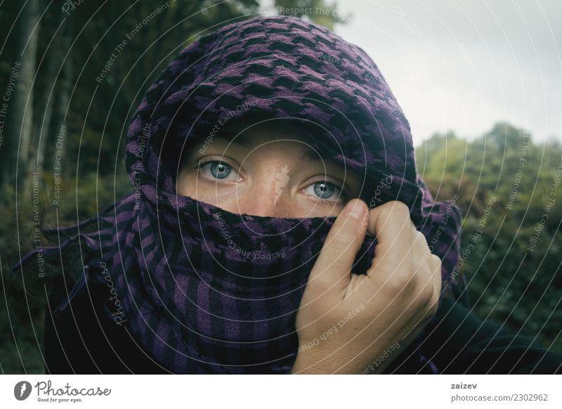Chica de ojos azules mirando a camara tapandose la cabeza y parte de la cara con un pañuelo aguantado por su mano en la naturaleza. Lifestyle Exotic Face
