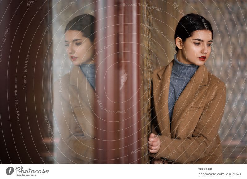 Woman with coat resting on tile wall and reflected in a glass Human being Youth (Young adults) Young woman Beautiful Calm 18 - 30 years Adults Wall (building)