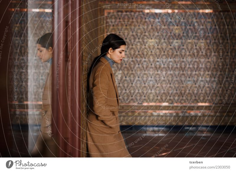 Woman with coat resting on tile wall and reflected in a glass Human being Youth (Young adults) Colour Calm 18 - 30 years Adults Wall (building) Feminine