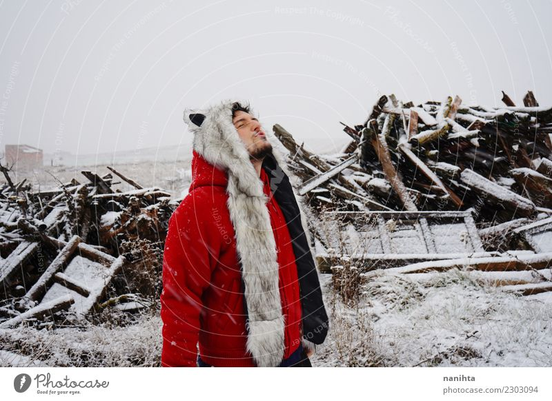 Young man with a fur hat enjoying a snowy day Human being Nature Youth (Young adults) Man White Red Joy Winter Adults Lifestyle Environment Cold Funny Natural