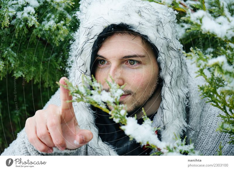 Young man touching a snowy branch Human being Nature Youth (Young adults) Man Green Tree Winter Adults Lifestyle Environment Healthy Cold Funny Snow Style