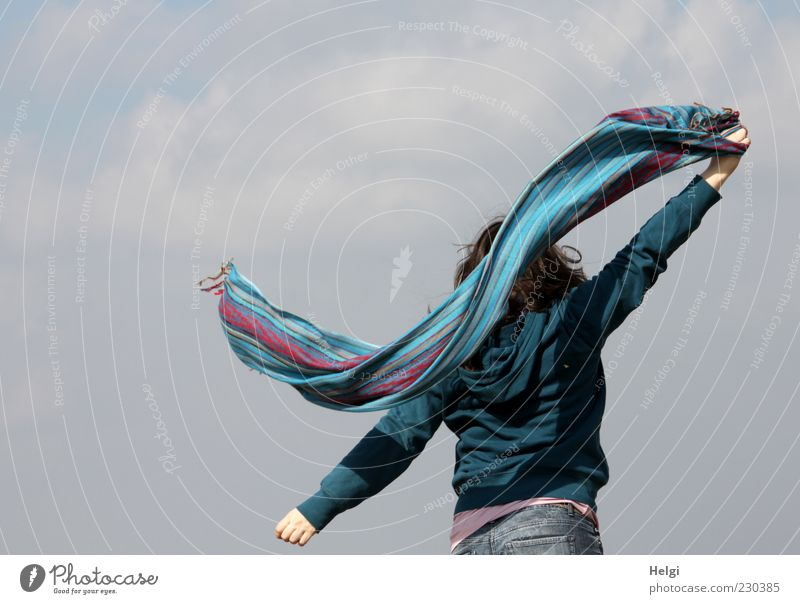 Rear view of a young woman swinging a colourful scarf in front of a grey sky Joy Life Well-being Contentment Leisure and hobbies Freedom Human being Feminine