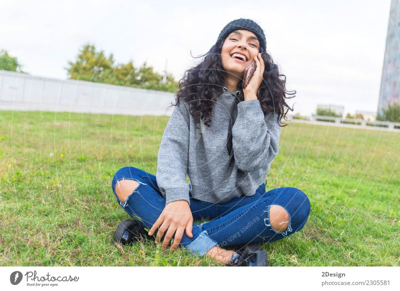Woman calling on phone sitting on the grass and smiling Youth (Young adults) Adults Lifestyle Emotions Grass Laughter Fashion Copy Space City life Modern
