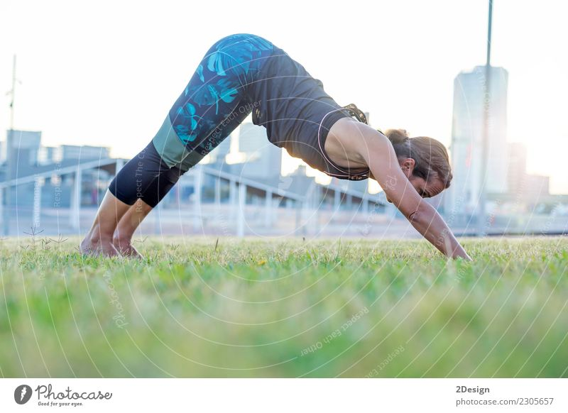 Beautiful girl is engaged in yoga in the park Lifestyle Harmonious Relaxation Sports Yoga Woman Adults Youth (Young adults) Nature Grass Park Sit Green Power