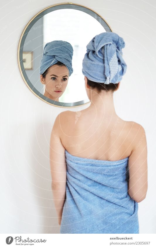 young woman wrapped in towel looks at herself in the mirror Lifestyle Beautiful Personal hygiene Wellness Flat (apartment) Mirror Bedroom Bathroom Human being