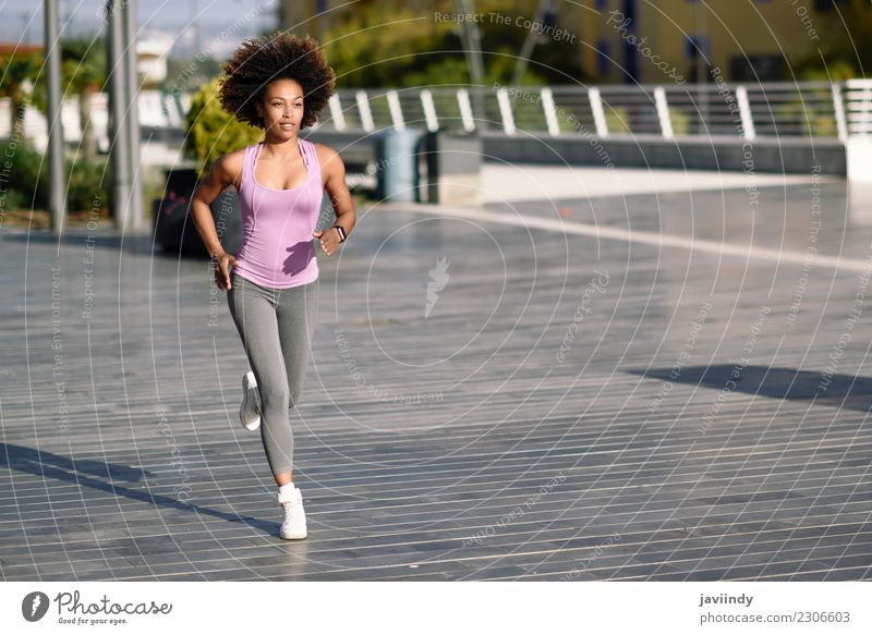 Black woman, afro hairstyle, running outdoors in urban road. Lifestyle Beautiful Hair and hairstyles Wellness Leisure and hobbies Sports Jogging Human being