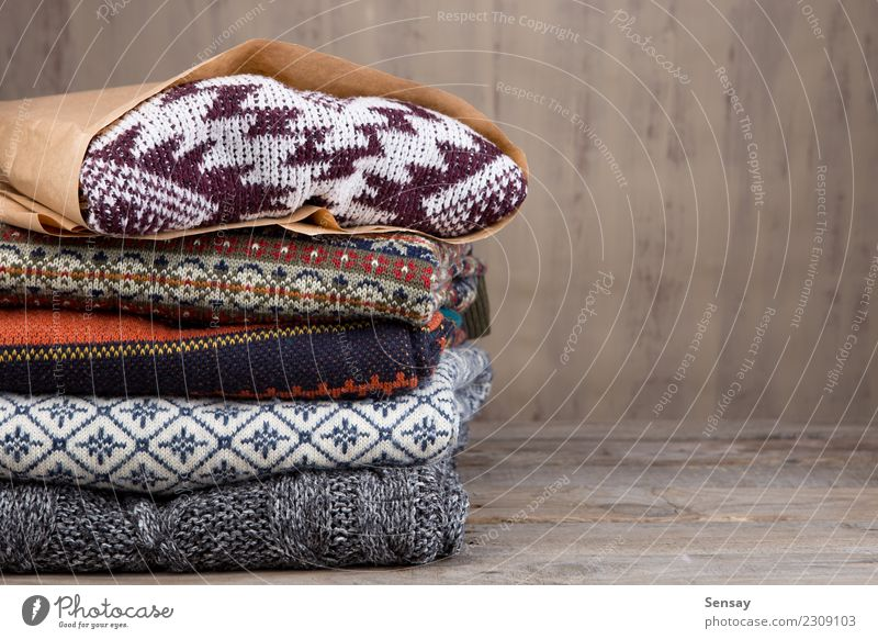 Pile of knitted winter sweaters on wooden background Lifestyle Shopping Style Knit Winter Desk Table Industry Autumn Warmth Fashion Clothing Sweater Wood Soft
