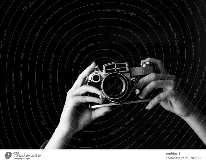 hands holding old analogue camera, taking photos taking pictures retro focus vintage shot equipment click black and white black background photographing