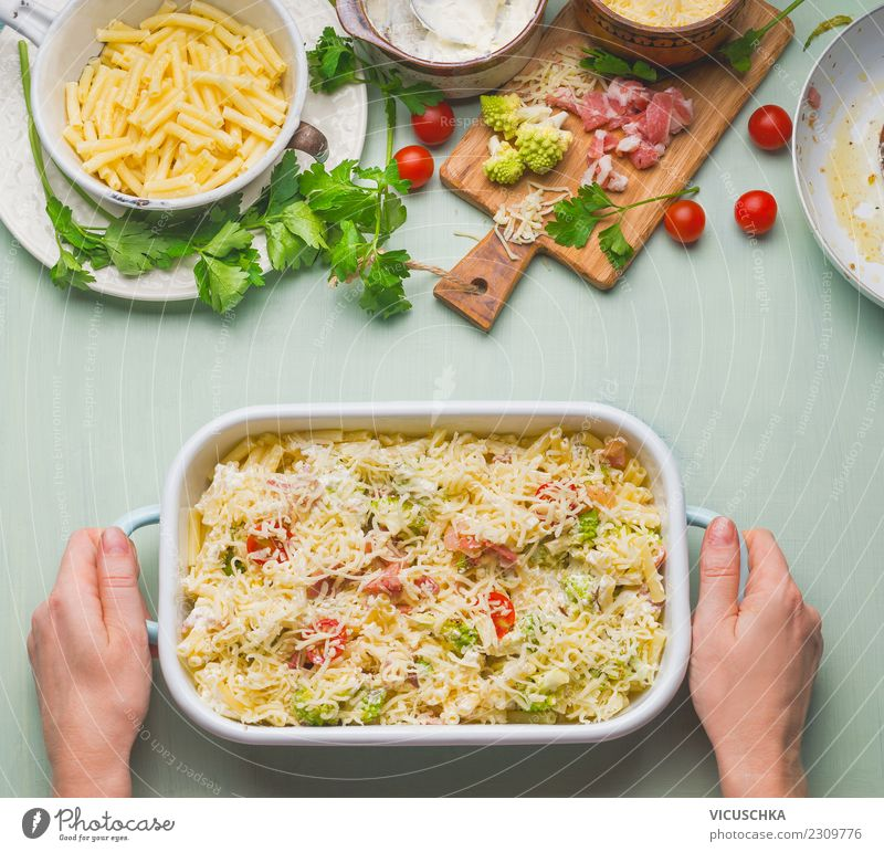 Female hands holding casserole dish with pasta casserole Food Lunch Dinner Crockery Style Design Table Kitchen Feminine Woman Adults Hand Yellow Macaroni