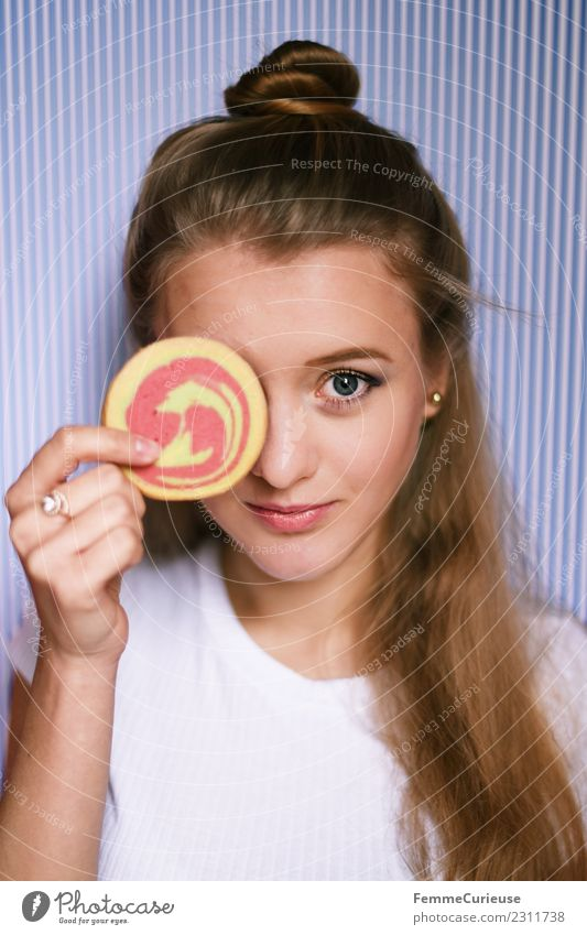 Young woman holding a cookie in front of her face Feminine Youth (Young adults) Woman Adults 1 Human being 18 - 30 years To enjoy Cookie Butter cookie