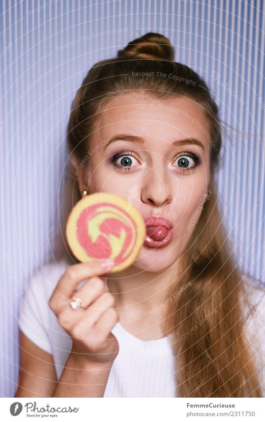 Young blonde woman showing a cookie Feminine Young woman Youth (Young adults) Woman Adults 1 Human being 18 - 30 years Joy Stick out Tongue Cookie Butter cookie