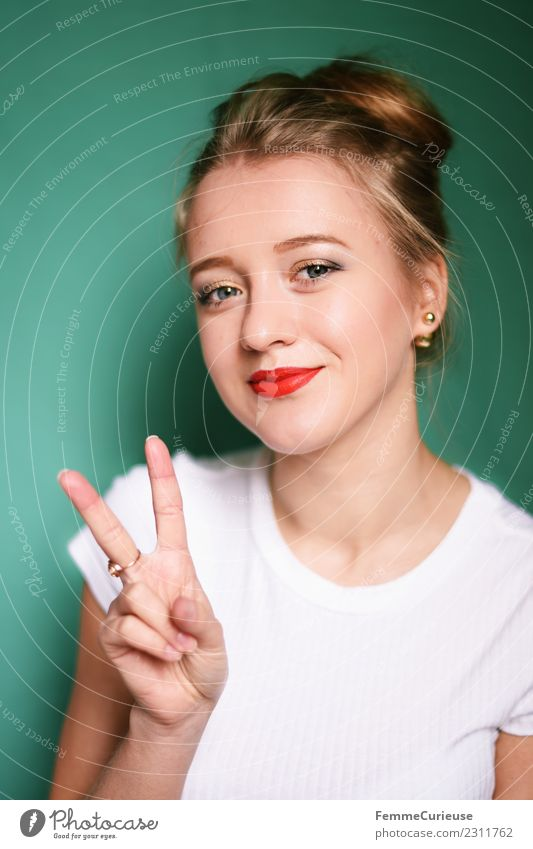 Young blonde woman showing the peace sign Young woman Youth (Young adults) Woman Adults 1 Human being 18 - 30 years Beautiful Peace Sign Fingers Hand Chignon