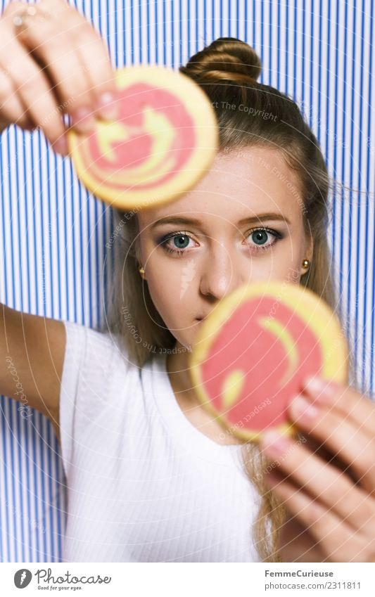 Young blonde woman holding two cookies in her hands Feminine Young woman Youth (Young adults) Woman Adults 1 Human being 18 - 30 years Leisure and hobbies Joy